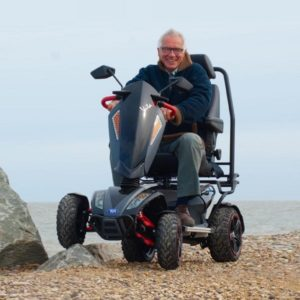 Mobility scooter on the beach drive by older man