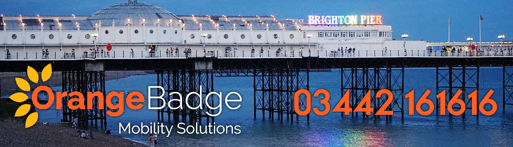 brighton pier at night with orange badge mobility services logo and number for the mobility products in brighton page
