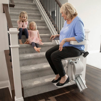 A woman sits on her bruno elan stairlift talking to her grandchioldrev