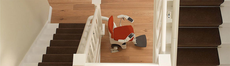 A red seated stairlift sits at the bottom of a long curved rail with multiple bends in it