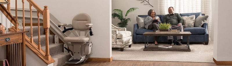 A happy couple sit on their sofa in the lounge with their stairlift parked at the bottom of the stairs in the foreground