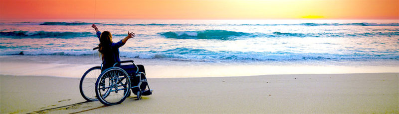 A woman sits on the beach in a wheelchair gazing out to sea admiring the sunset. Her arms are spread wide.